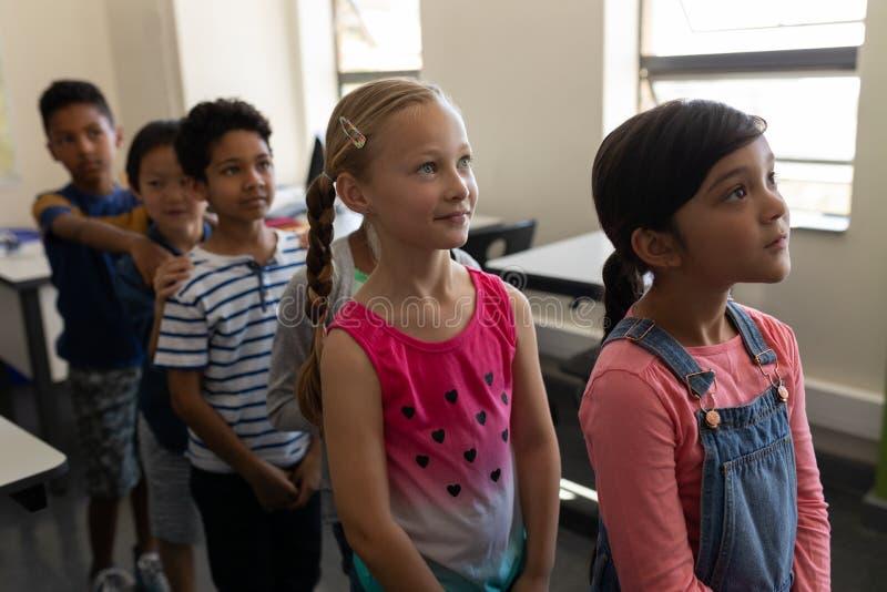 Niños de la escuela que se colocan en fila en sala de clase de la escuela primaria fotos de archivo libres de regalías