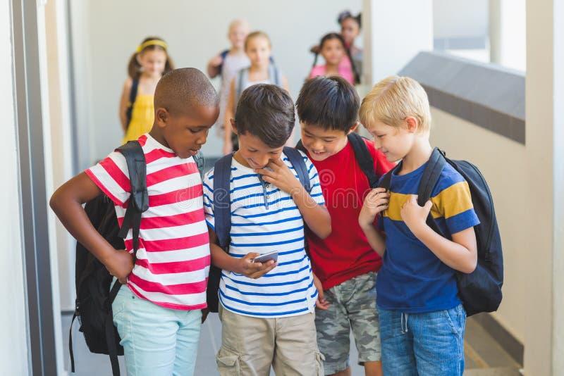 Niños de la escuela usando el teléfono móvil en pasillo fotos de archivo libres de regalías