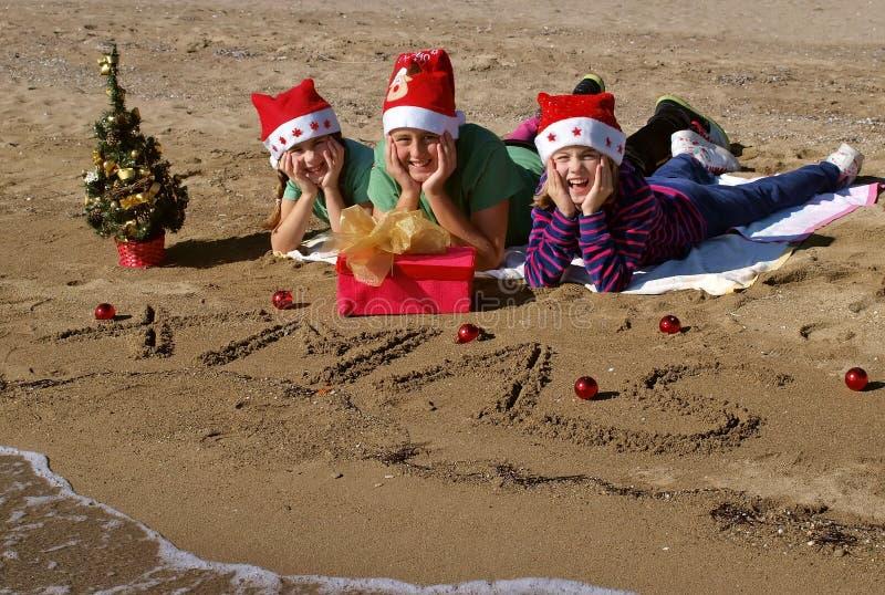 Niños de la feliz Navidad en la playa foto de archivo