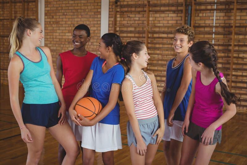 Niños de la High School secundaria que se divierten en cancha de básquet imágenes de archivo libres de regalías