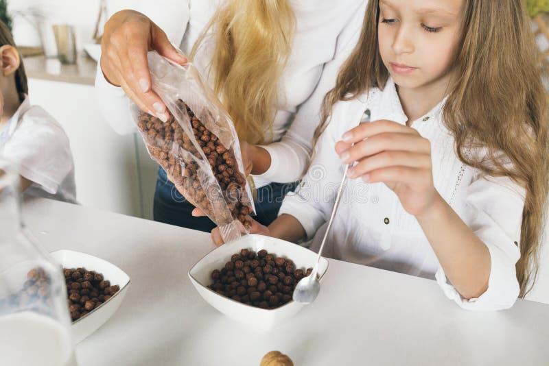 Niños de la madre que comen la familia de amor feliz del desayuno de la cocina sana del hogar imágenes de archivo libres de regalías