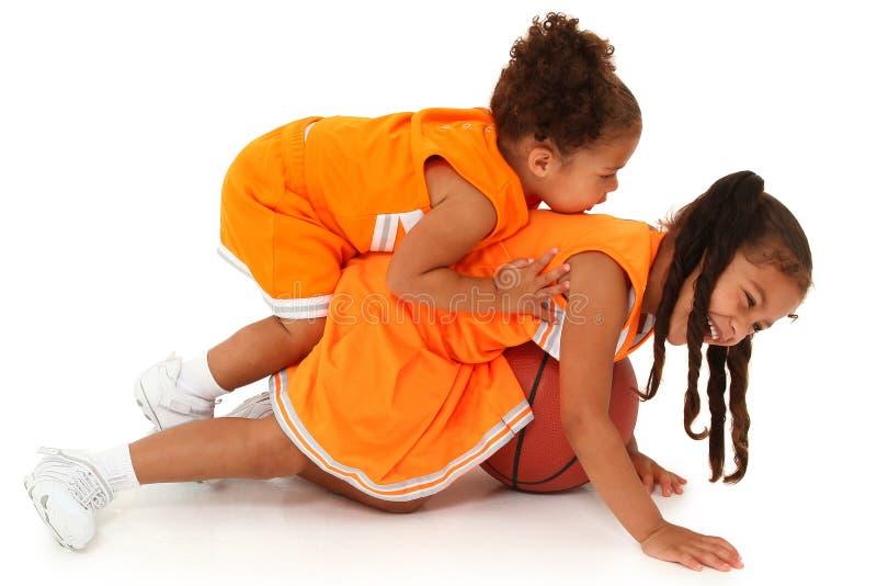 Niños de la muchacha de la hermana en el uniforme que juega a baloncesto imágenes de archivo libres de regalías