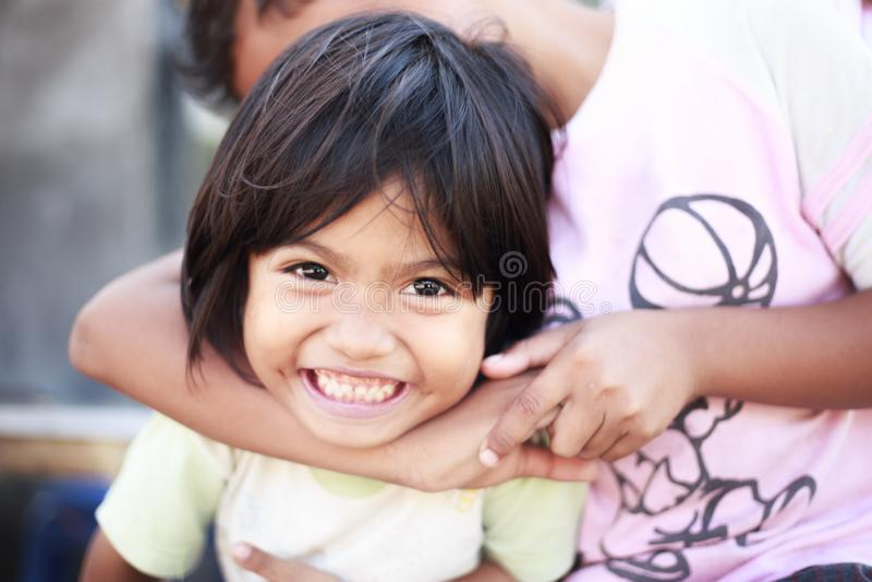 Niños de la pobreza que juegan feliz al aire libre en un pueblo a pesar de la vida pobre imágenes de archivo libres de regalías