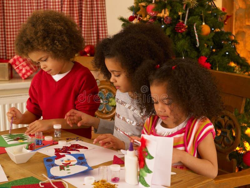 Niños de la raza mezclada que hacen tarjetas de Navidad fotografía de archivo