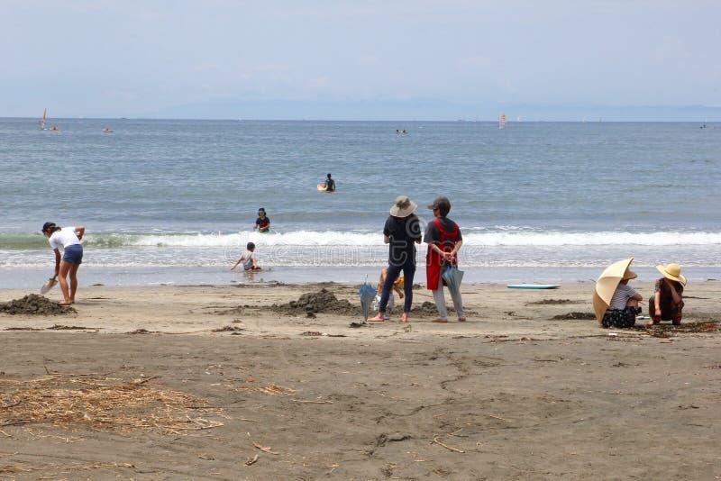 Niños de las familias que juegan el mar de la playa arenosa, Kamakura, Japón fotografía de archivo libre de regalías