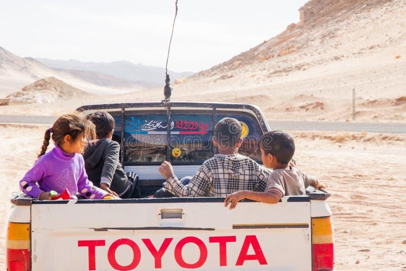 Niños de los beduinos en jeep en el desierto, desierto de Egipto, Sinaí imagen de archivo
