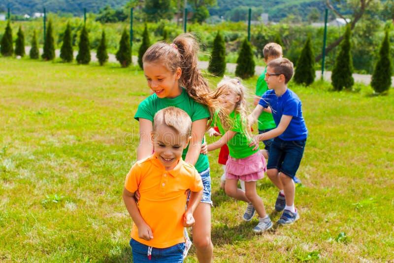 Niños de risa que juegan la cola de un dragón foto de archivo