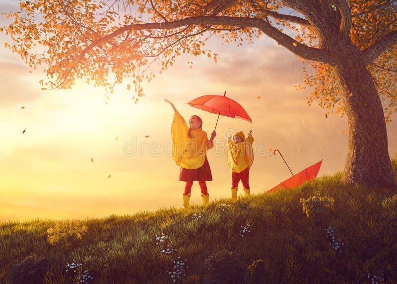 Niños debajo de la ducha del otoño fotos de archivo libres de regalías