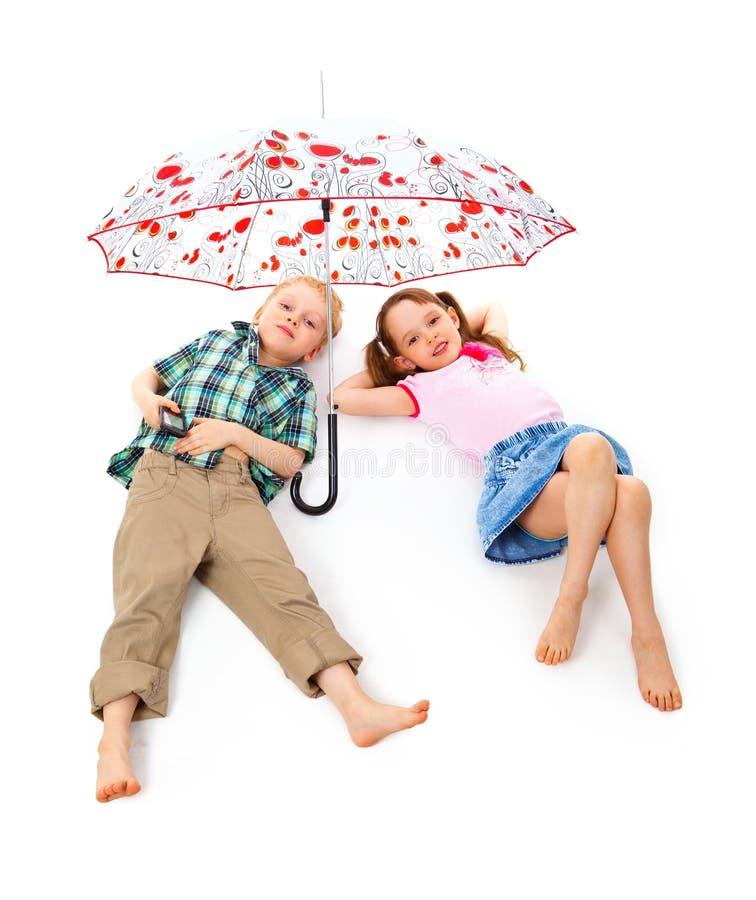 Niños debajo de un paraguas foto de archivo libre de regalías