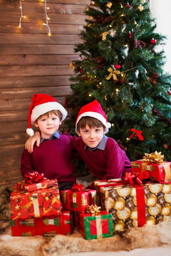 Niños debajo del árbol de navidad con las cajas de regalo imagen de archivo libre de regalías