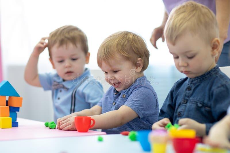 Niños del cuarto de niños que juegan con la arcilla del juego en la guardería o el playschool foto de archivo