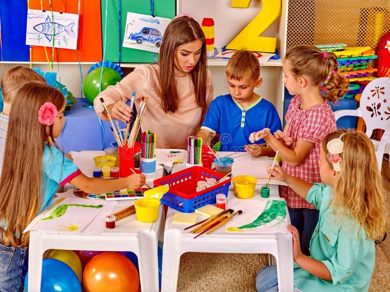 Niños del grupo con el profesor en preescolar imagenes de archivo