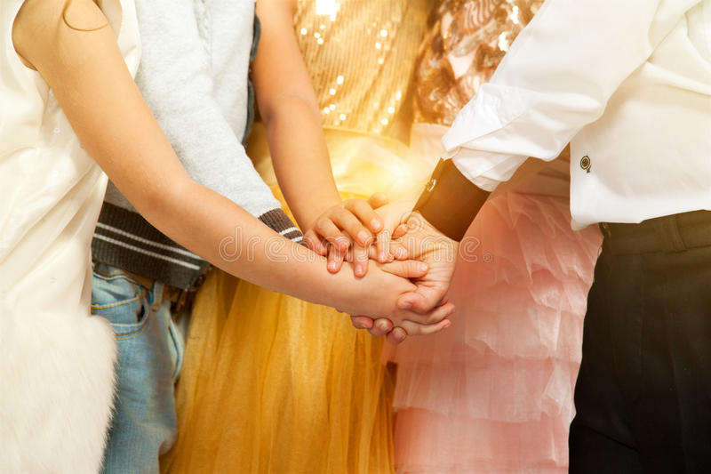 Niños del grupo en la ropa del día de fiesta que lleva a cabo las manos Amistad, concepto de la moda fotografía de archivo