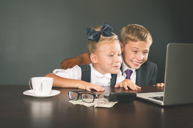 Niños del negocio, niños que usan el ordenador portátil Juegos de Internet imágenes de archivo libres de regalías