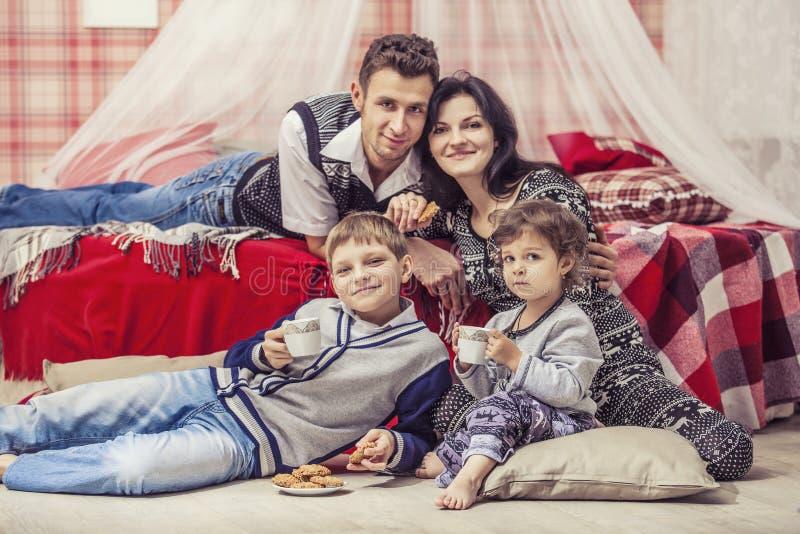 Niños del padre de la madre de la familia en el dormitorio en casa que beben el te imagen de archivo libre de regalías