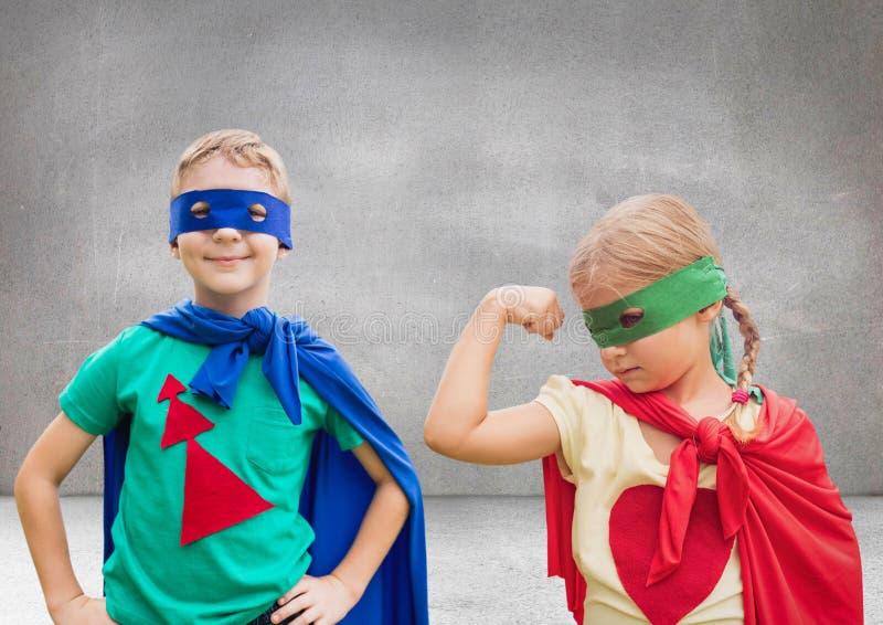 Niños del super héroe con el fondo gris en blanco imagen de archivo