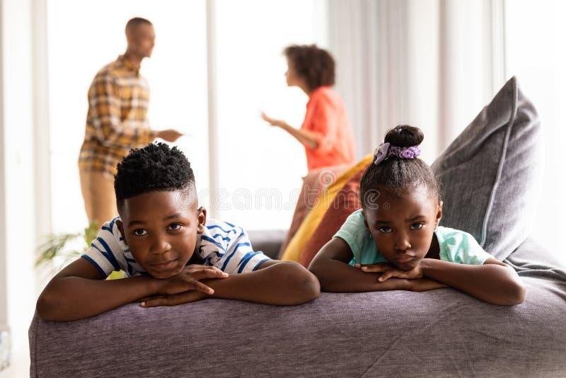 Niños del trastorno que se sientan en un sofá mientras que sus padres que discuten en el fondo fotos de archivo
