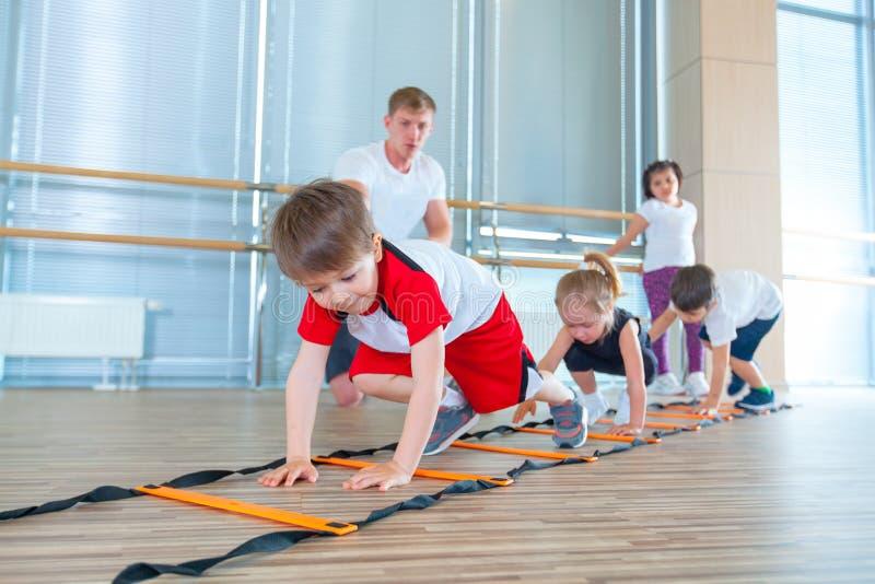 Niños deportivos felices en gimnasio Ejercicios de los niños imagen de archivo