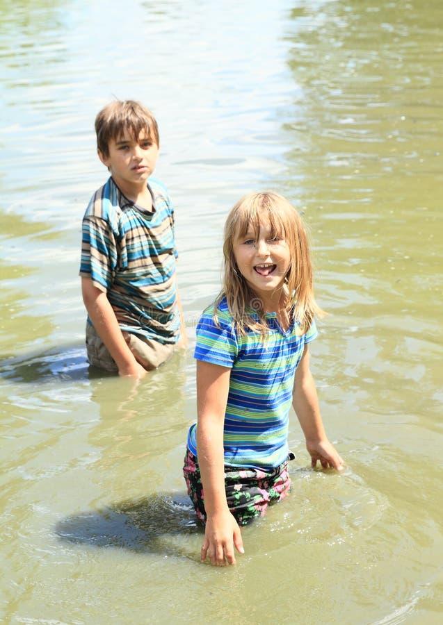 Niños desagradables en la impregnación de la ropa mojada en agua imagen de archivo libre de regalías