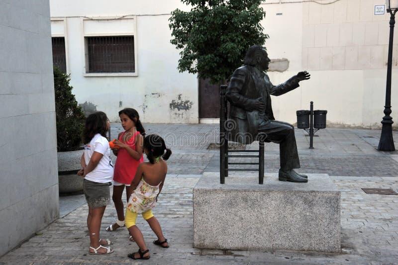Niños desconocidos en el monumento al flamenco español famoso Chano Lobato del cantante en el centro del ` de Merced del La del ` imagen de archivo