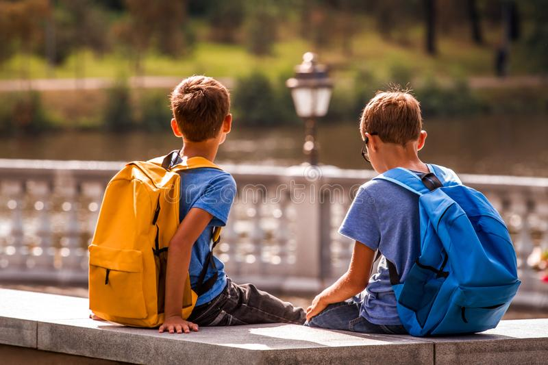 Niños después de la escuela, sentándose en banco y hablar Educación, de nuevo a escuela, amistad, niñez, comunicación y foto de archivo