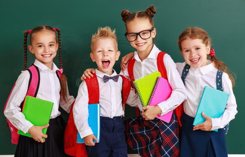 Niños divertidos colegial y colegiala, muchacho del estudiante y muchacha del grupo sobre la pizarra de la escuela foto de archivo libre de regalías