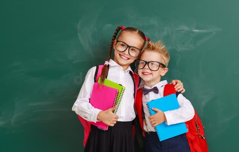 Niños divertidos colegial y colegiala, muchacho del estudiante y muchacha del grupo sobre la pizarra de la escuela imágenes de archivo libres de regalías