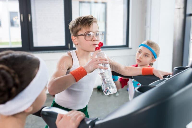 Niños divertidos en el entrenamiento de la ropa de deportes en la rueda de ardilla en el gimnasio junto fotos de archivo libres de regalías