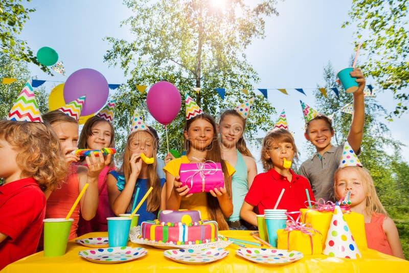 Niños divertidos que animan a la muchacha del cumpleaños en el parque del verano foto de archivo