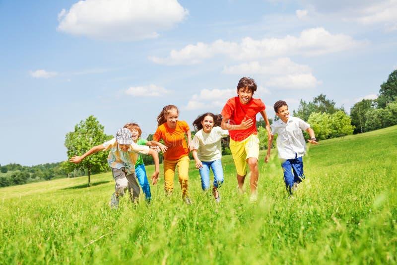 Niños divertidos que corren en el campo fotos de archivo