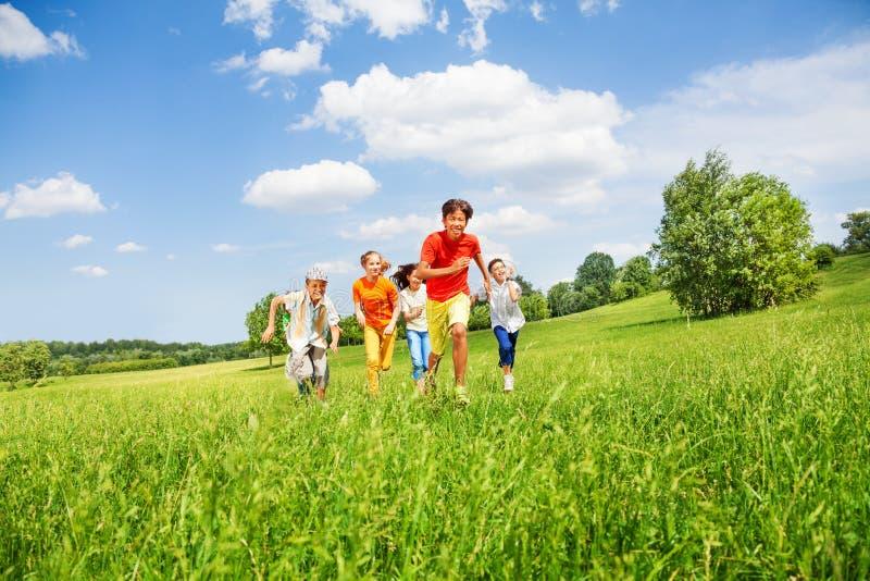 Niños divertidos que corren junto en el campo imágenes de archivo libres de regalías