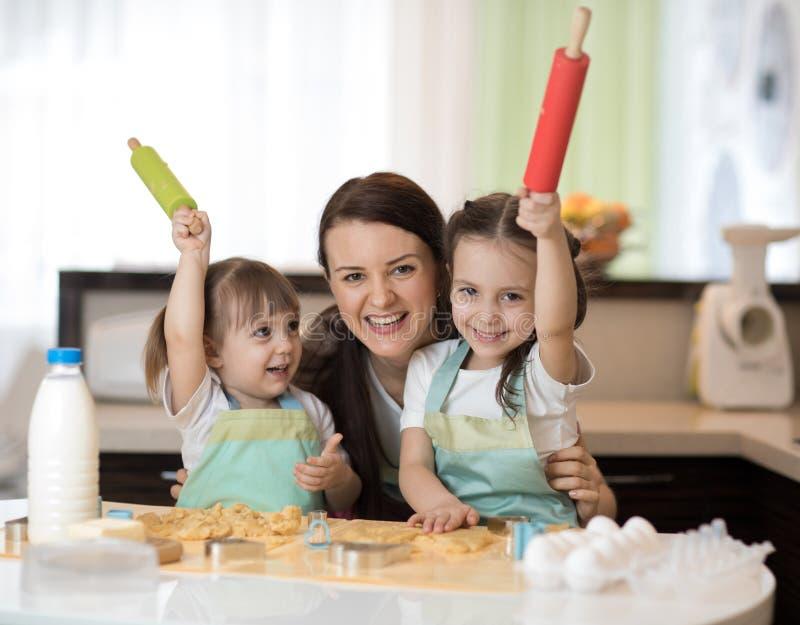 Niños divertidos que cuecen las galletas con su madre fotografía de archivo