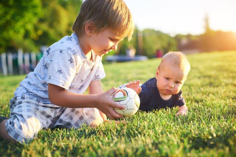 Niños divertidos que juegan con la bola en hierba verde en la naturaleza en el día de verano Dos hermanos al aire libre Muchacho  foto de archivo libre de regalías