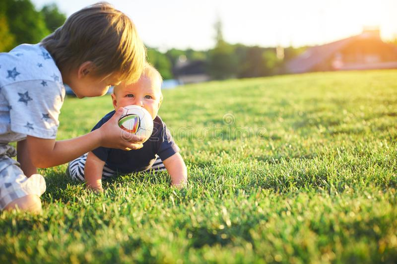 Niños divertidos que juegan con la bola en hierba verde en la naturaleza en el día de verano Dos hermanos al aire libre Muchacho  imagen de archivo