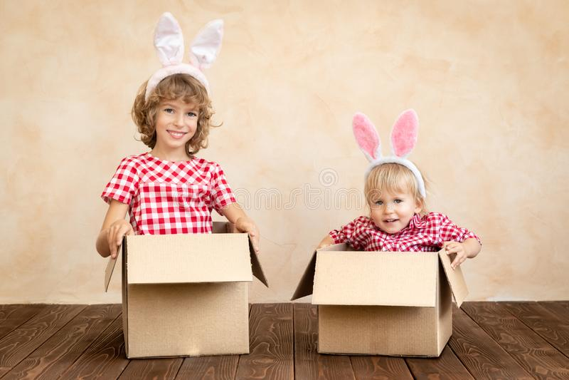 Niños divertidos que llevan el conejito de pascua fotografía de archivo