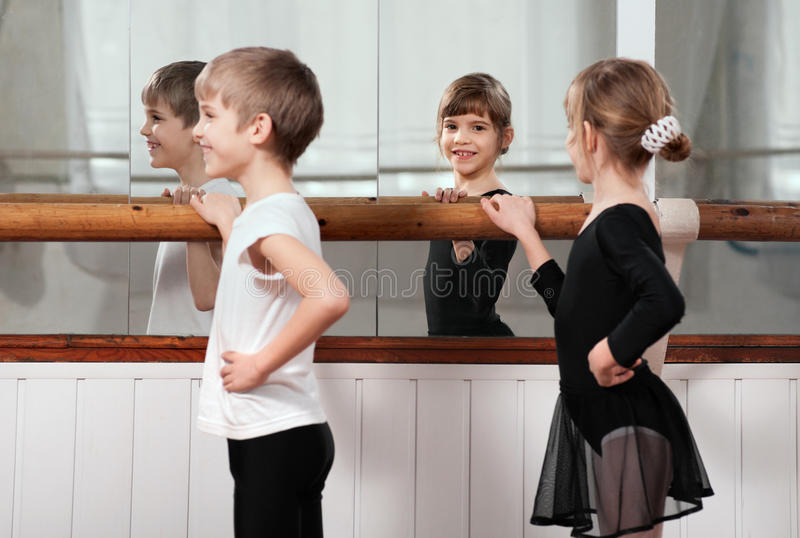 Niños que se colocan en la barra del ballet imagenes de archivo