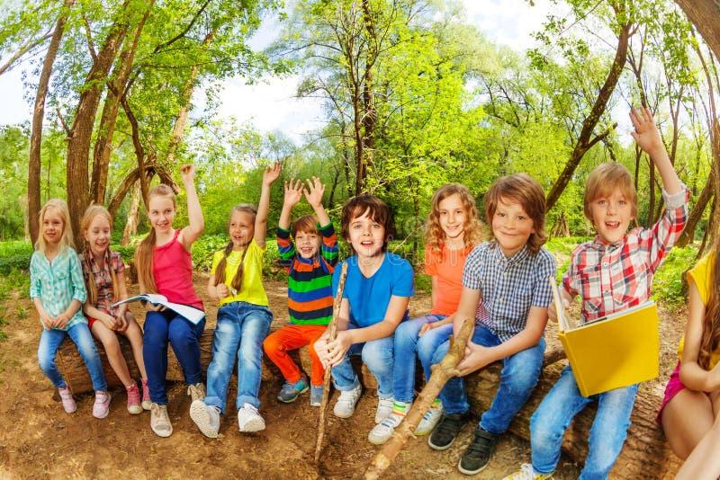 Niños divertidos que se sientan en el registro al aire libre y el libro de lectura fotografía de archivo libre de regalías