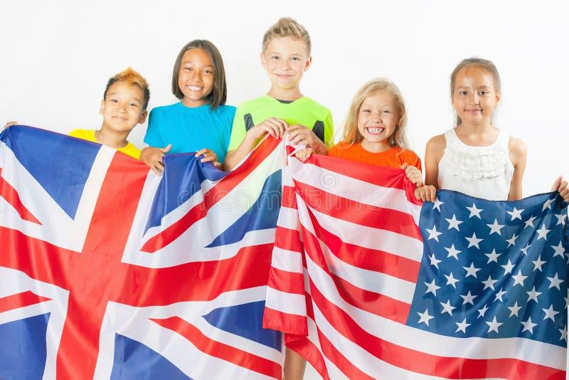 Niños divertidos que sostienen la bandera Gran Bretaña y la bandera nacional americana fotos de archivo libres de regalías