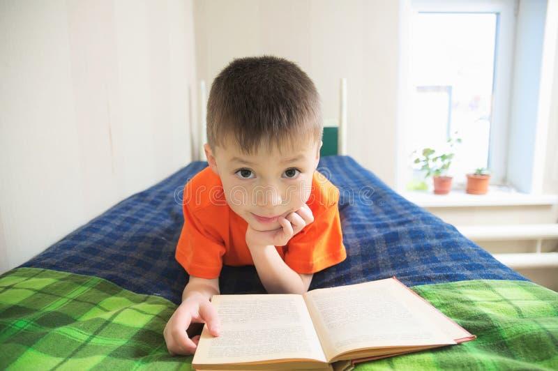 Niños educación, libro de lectura del muchacho que miente en la cama, retrato del niño que sonríe con el libro, guión interesante imágenes de archivo libres de regalías