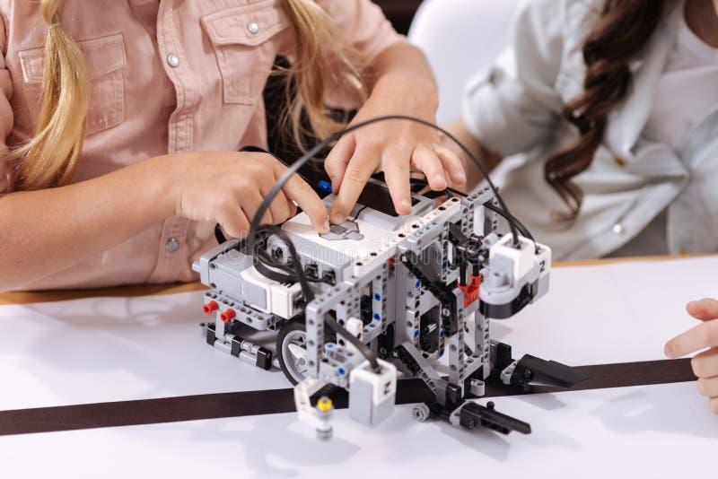 Niños elegantes que prueban el robot en la escuela fotografía de archivo