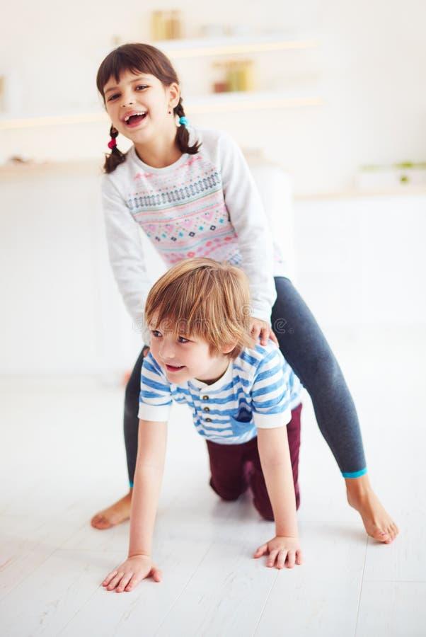 Niños emocionados felices que se divierten, montando en la parte posterior en casa imagen de archivo