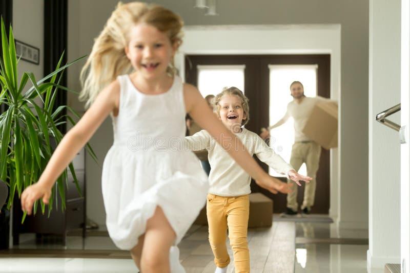 Niños emocionados que corren en la cámara, familia que se mueve en nueva casa foto de archivo