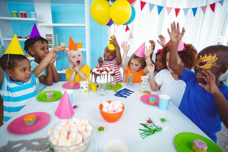 Niños emocionados que disfrutan de una fiesta de cumpleaños imagen de archivo libre de regalías