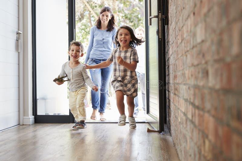 Niños emocionados que llegan a casa con los padres imagen de archivo libre de regalías