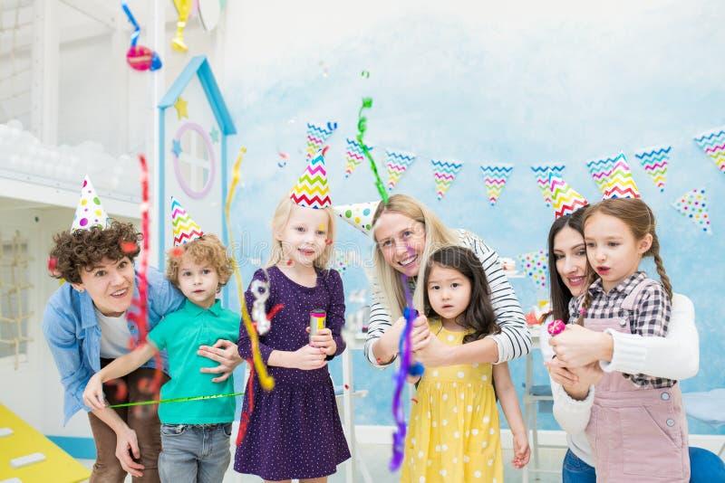 Niños emocionados que miran confeti que cae de las galletas imagen de archivo libre de regalías