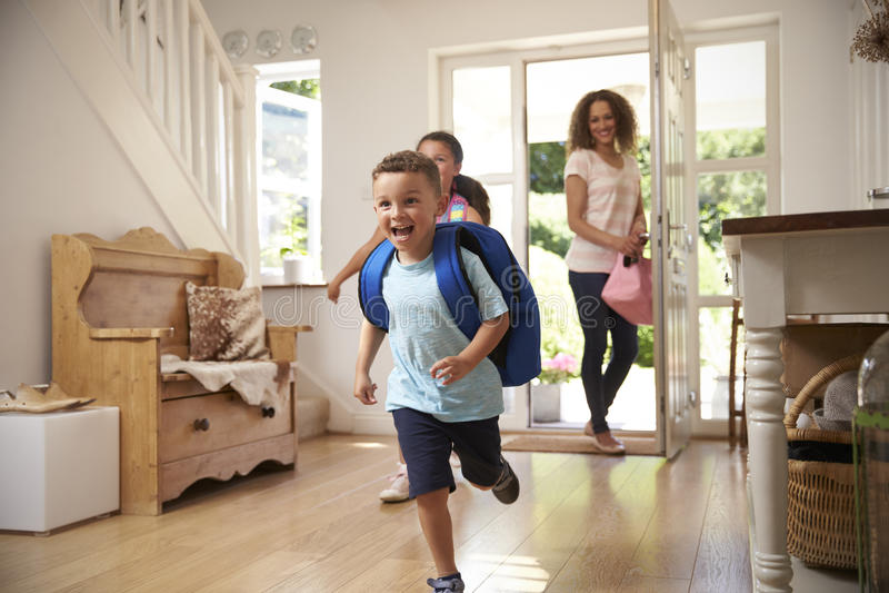 Niños emocionados que vuelven a casa de escuela con la madre imágenes de archivo libres de regalías