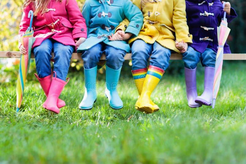 Niños en botas de lluvia Desgaste del pie para los niños fotos de archivo