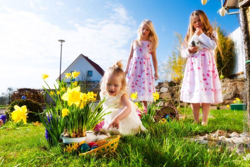 Niños en caza del huevo de Pascua con el conejito fotos de archivo