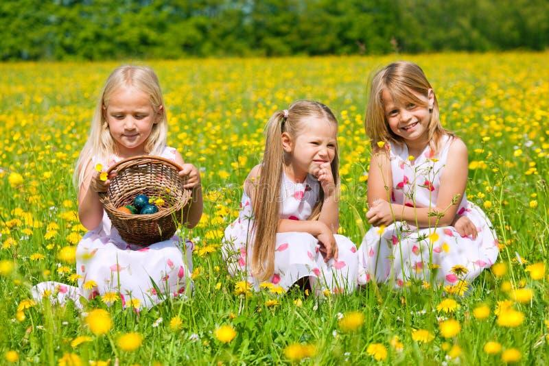 Niños en caza del huevo de Pascua con los huevos fotografía de archivo libre de regalías
