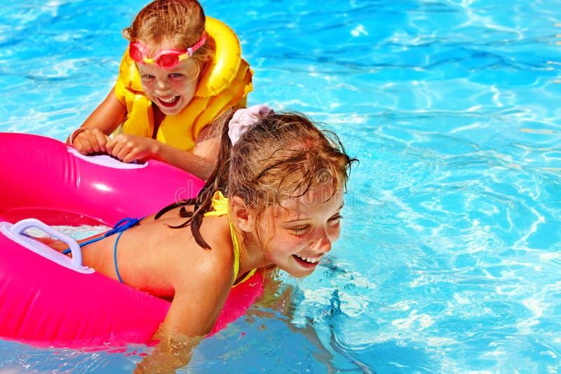 Niños en chaleco salvavidas en piscina foto de archivo